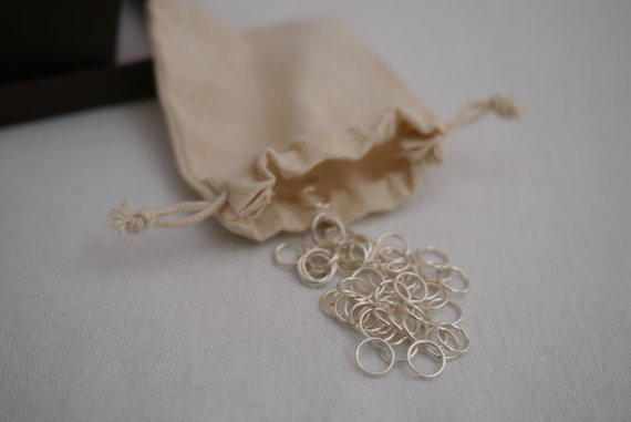 silver jump rings spilling out of a bag