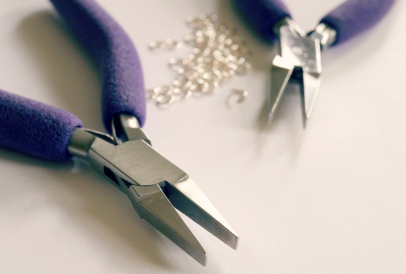 two pairs of purple pliers with silver jump rings in the background