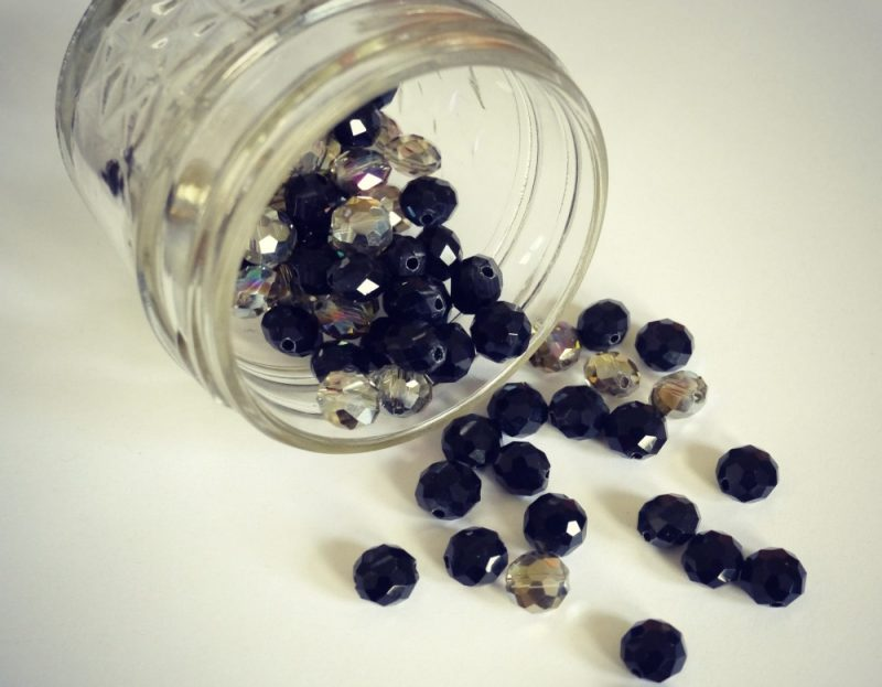 black and clear beads spilling out of a jar