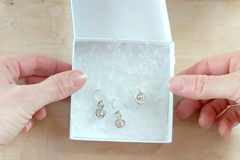 hands holding gift box with pink and silver freshwater pearl earring necklace set