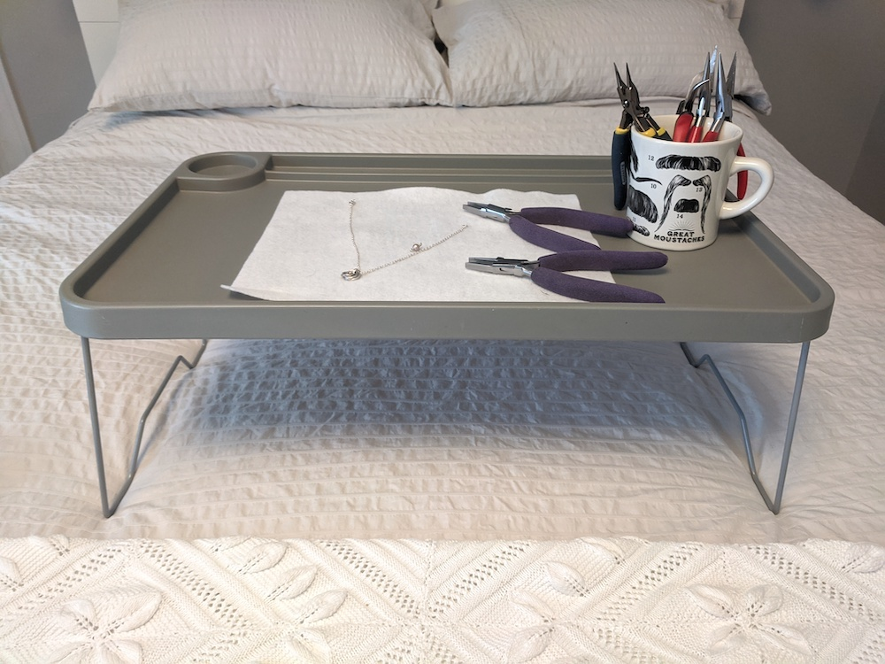 folding tray on a bed with jewelry making supplies